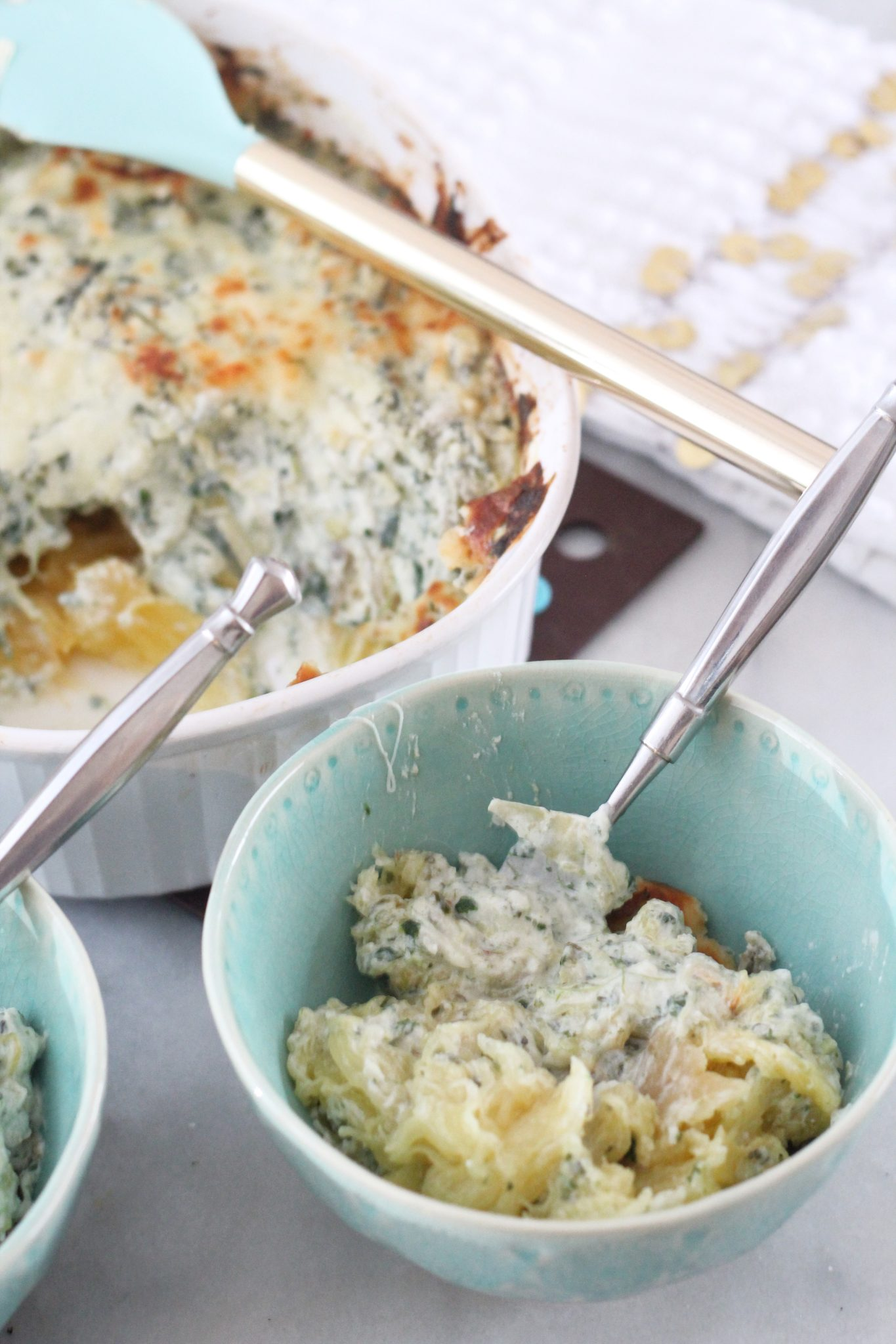 This recipe for Creamy Spinach Artichoke Spaghetti Squash Casserole tastes just like your favorite dip, but melted over healthy spaghetti squash! It's low carb and keto! #lowcarbdelish #lowcarbdinner #lowcarbcasserole #ketodinner #ketodinnerrecipes #lowcarbrecipes #spaghettisquashrecipes