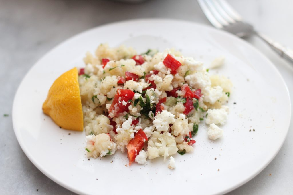 keto cauliflower riced with peppers, parsley and feta with lemon wedge
