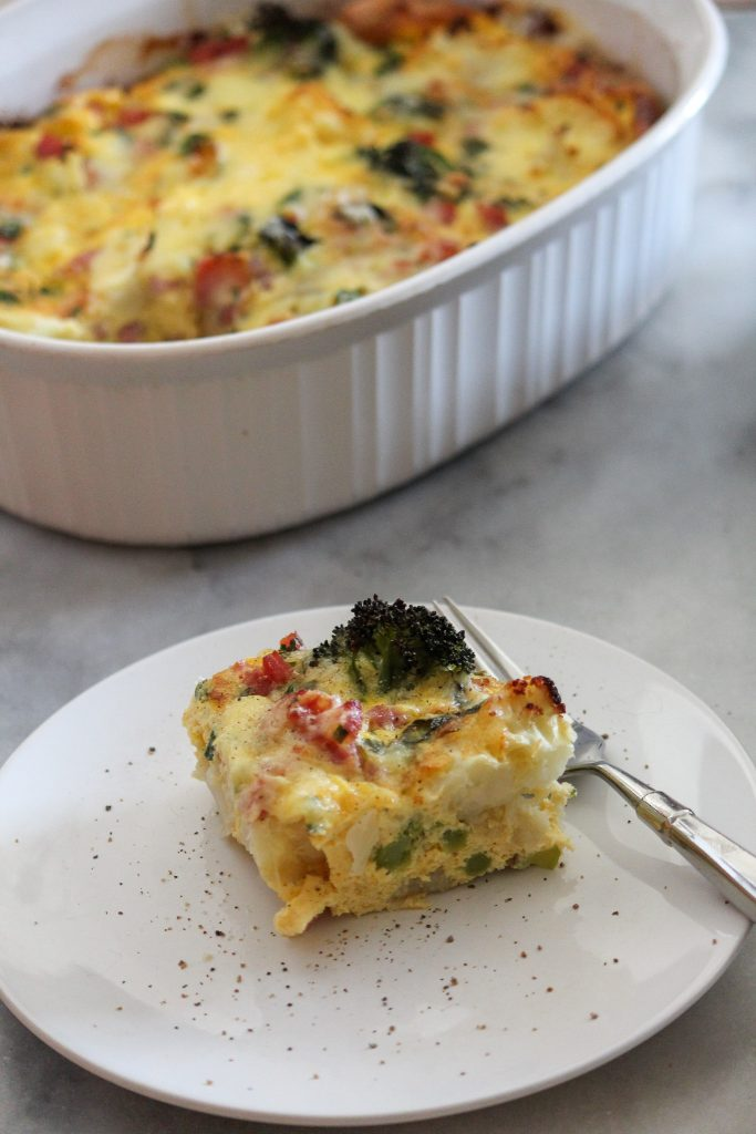 Slice of low carb breakfast casserole on a white plate with fork.