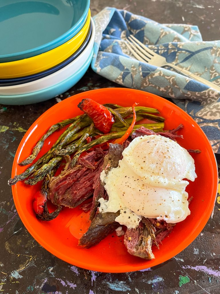 Poached eggs on top of corned beef and some roasted asparagus in an orange bowl.