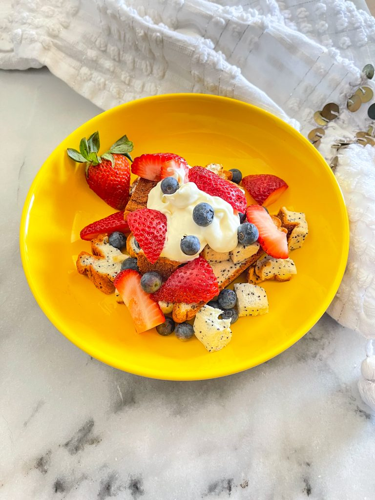 This image shows a yellow bowl with protein poppy seed loaf with berries and cream.