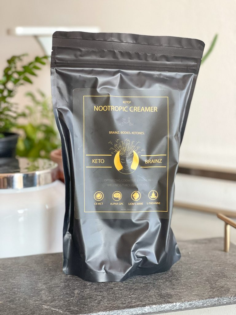 Image of a bag of Keto Brainz nootropic creamer with plants in the background.