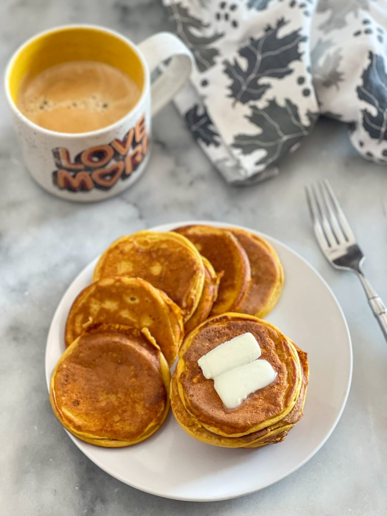 This image depicts pumpkin protein pancakes on a white plate with a pat of butter and a fork and cup of coffee off to the side.
