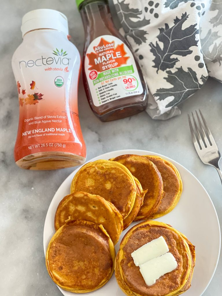 This image depicts pumpkin protein pancakes on a plate and Nectevia and All-u-Lose maple flavor syrups.