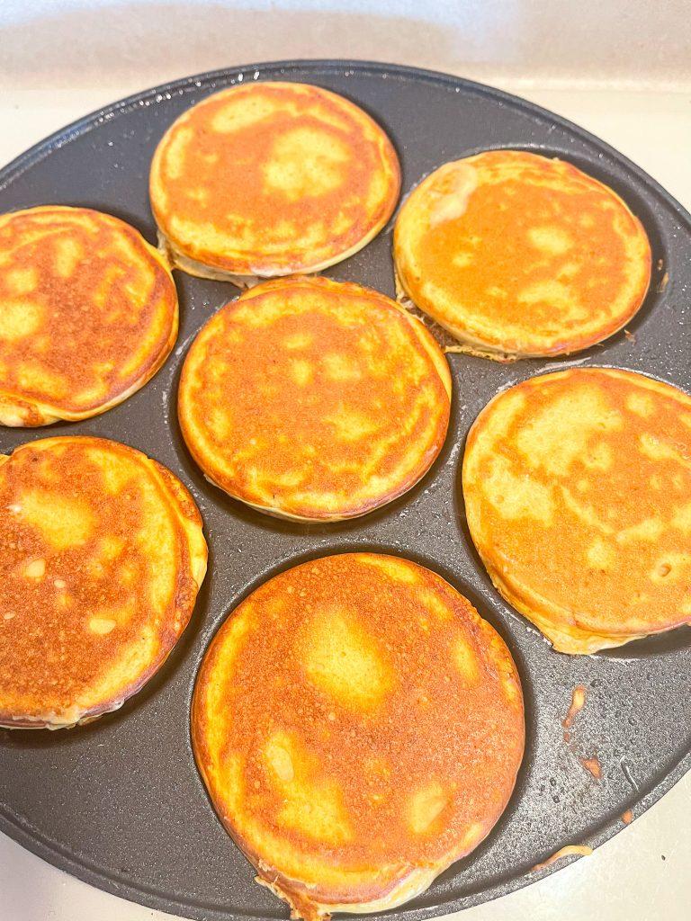 This image depicts pancakes cooking in dollar pancake pan.