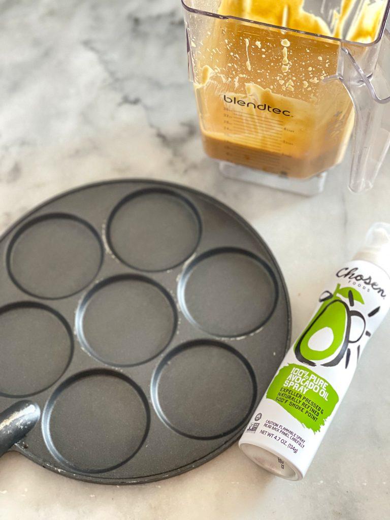 This image depicts the dollar pancake pan, Chosen Foods avocado oil spray and the pumpkin protein pancake batter in the blender jar.