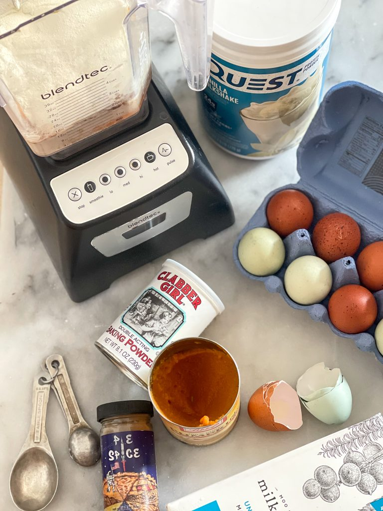 This image shows the ingredients for the pumpkin protein pancakes, including eggs, protein powder, pumpkin purée, milkadamia, baking powder and a blender.