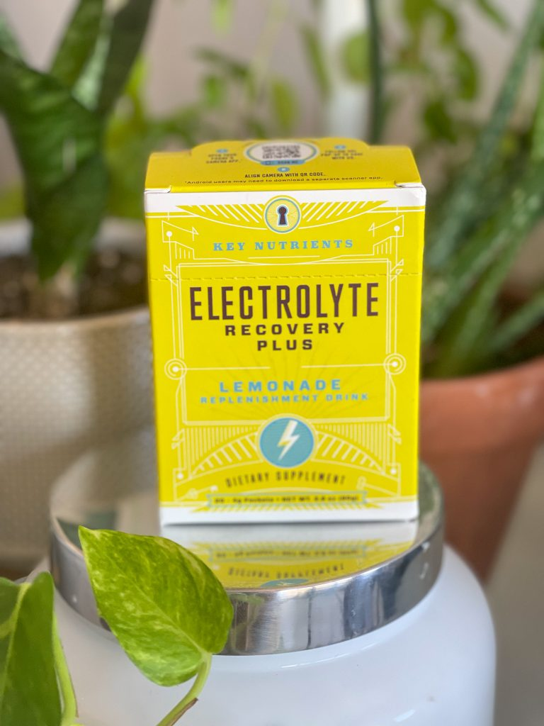 Image of a box of Key Nutrients electrolytes powder with plants in the background.