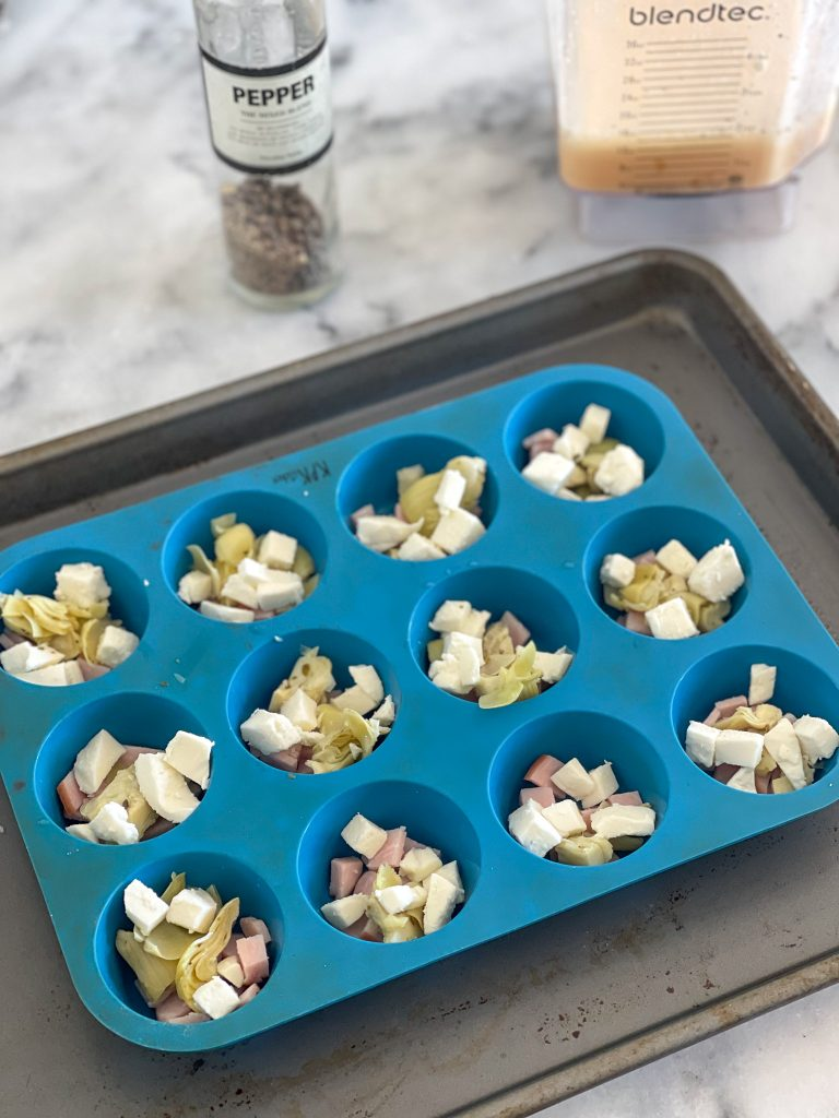 This image depicts a blue muffin tray with diced Canadian bacon, artichoke hearts and mozzarella in each cup. There is a blender with eggs in it and a pepper mill in the background.